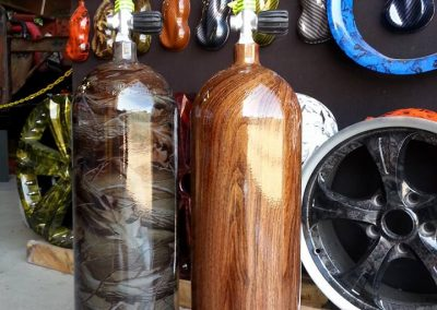 Steel scuba diving tanks done in a camouflage and a woodgrain design.