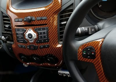An example of a black carbon fibre design with an orange base coat on interior dash panels.