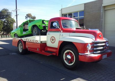 After shot of a complete restoration on 1951 Diamond T Truck along with a restoration of green Plymouth Roadrunner on the back.