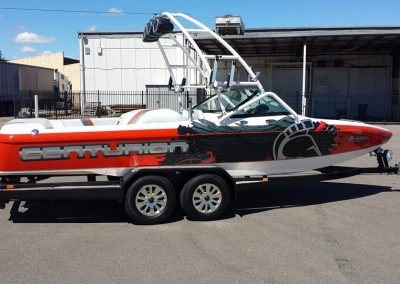 After shot of Centurion ski boat with orange paint and custom stickers.