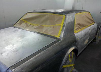 During shot of closed door, bare metal insurance job on Bentley.